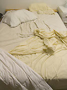 unmade bed in bedroom with disheveled sheets