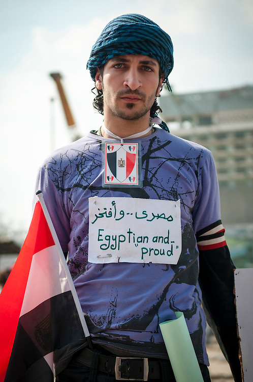 An anti-Mubarak demonstrator in Tahrir Square, holding a flag and wearing a homemade sign that reads EGYPTIAN AND PROUD in both English and Arabic.