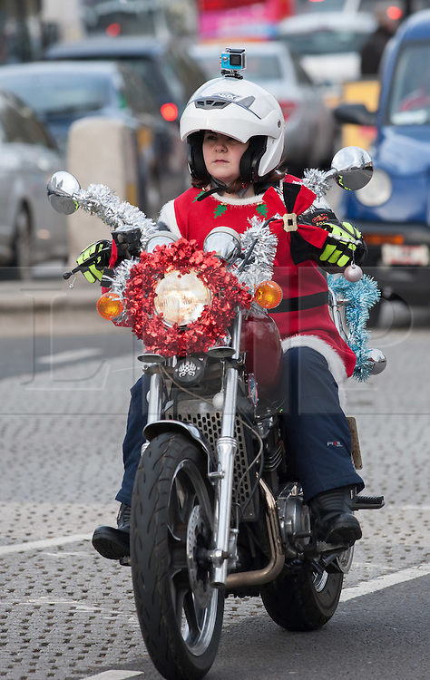 © Licensed to London News Pictures. 05/12/2015. Bristol, UK.  The 2015 Bristol Santas on a Bike ride through Bristol city centre from locations in the West of England, heading for the Children's Hospice South West near Bristol. The ride is to raise money to give a merry Christmas to some great children and their families at the Children's Hospice South West near Bristol.  Photo credit : Simon Chapman/LNP