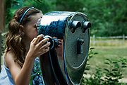 Girl looking through a viewing scope.