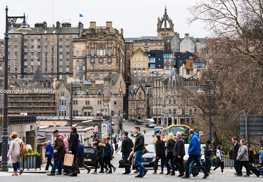 Pedestrians crossing street with Old Town to rear in central Edinburgh, Scotland, UK