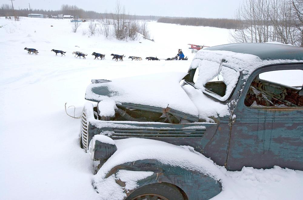 USA, Alaska, Anvik, Musher Martin Buser and dog sled team race past abandoned snow-covered truck along Yukon River on winter morning during 2005 Iditarod sled dog race