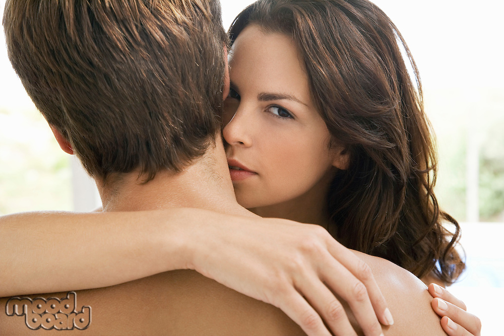 Woman embracing man looking over his shoulder head and shoulders