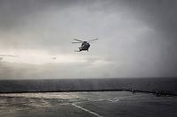 "INTERNATIONAL WATERS (OFF THE COASTS OF SICILY, ITALY) - 9 FEBRUARY 2017: A SH-90 helicopter of the Italian Navy approaches the San Giorgio, an amphibious transport dock of the Italian Navy, in international waters off the coast of Sicily, Italy, on Febuary 9th 2017.<br /> <br /> As a consequence of the April 2015 Libya migrant shipwrecks, the EU launched a military operation known as European Union Naval Force Mediterranean (EUNAVFOR Med), also known as Operation Sophia, with the aim of neutralising established refugee smuggling routes in the Mediterranean. The aim of this new operation launched by Europe is to undertake systematic efforts to identify, capture and dispose of vessels as well as enabling assets used or suspected of being used by migrant smugglers or traffickers. On 20 June 2016, the Council of the European Union extended Operation Sophia's mandate reinforcing it by supporting the training of the Libyan coastguard.<br /> Thus far, following EUNAVFOR MED operation Sophia's activities, 101 suspected smugglers and traffickers have been apprehended and transferred to the Italian<br /> authorities and 380 boats were removed from the criminal organizations' availability. The Operation has saved 32.081 migrants, among whom 1888 children.<br /> <br /> On February 2nd 2017 Italian Premier Paolo Gentiloni and Prime Minister of the U.N. backed Libyan government Fayez al-Serraj signed a memorandum of understanding on cooperation to combat illegal migration, human trafficking and contraband and on reinforcing the border between Libya and Italy. The following day, as EU leaders meet in Malta for a summit, European Council President Donald Tusk said after talks with Serraj, that ""it is time to close the (migrant) route from Libya to Italy"" and that ""the EU has shown it is able to close the routes of irregular migration, as it has done in the eastern Mediterranean.""  Tusk said the Central Mediterranean route was ""not sustainable either for the EU or for Libya"", where he said traffickers"