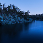 The C&O Canal (short for Chesapeake and Ohio) is seen at dusk along the towpath at Great Falls in Potomac, MD. <br /> <br /> The C&O Canal was created in the 1830's in an effort to connect the Ohio River Valley frontier with the East Coast. However, trains were beginning to come onto the scene around the time of construction. Beginning with the B&O Railroad based out of Baltimore, trains could carry much larger cargos than canal boats, travel faster and be constructed far easier than digging and dredging canals. Construction was halted at Cumberland Maryland, 100 miles west of Washington, as the railroad arrived at Pittsburgh, making the canals original purposes obsolete. Nonetheless, the canal was widely used for transportation of raw materials such as coal from mines in West Virginia. The canal fell into disuse by the 20th century, and the National Parks Service purchased the canal in the 1930's.