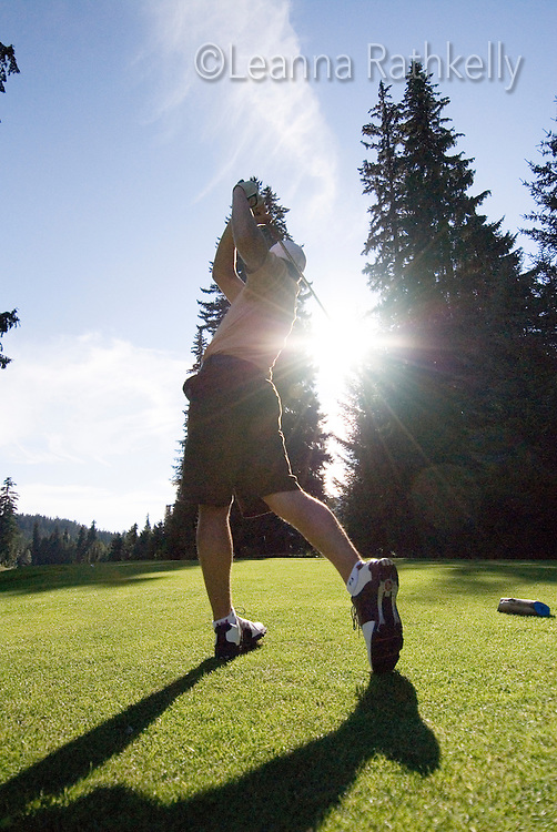 Teenage male golfer tees off on a sunny day on the Whistler Golf Course, Whistler, BC Canada.