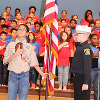 """East Amory Elementary School fifth-graders, Hayden Bryant, left, and Titus Abas, salute the flag to begin a  Veterans Day program at their school last week. The color guard and their class colleagues presented a program of songs and verse titled """"We the People."""""""