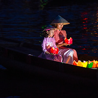 HOI AN , VIETNAM - OCT 04 : Vietnamese mother and daughter holding Lanterns before droping them into the River in Hoi An Vietnam during the Hoi An Full Moon Lantern Festival on October 04 2017