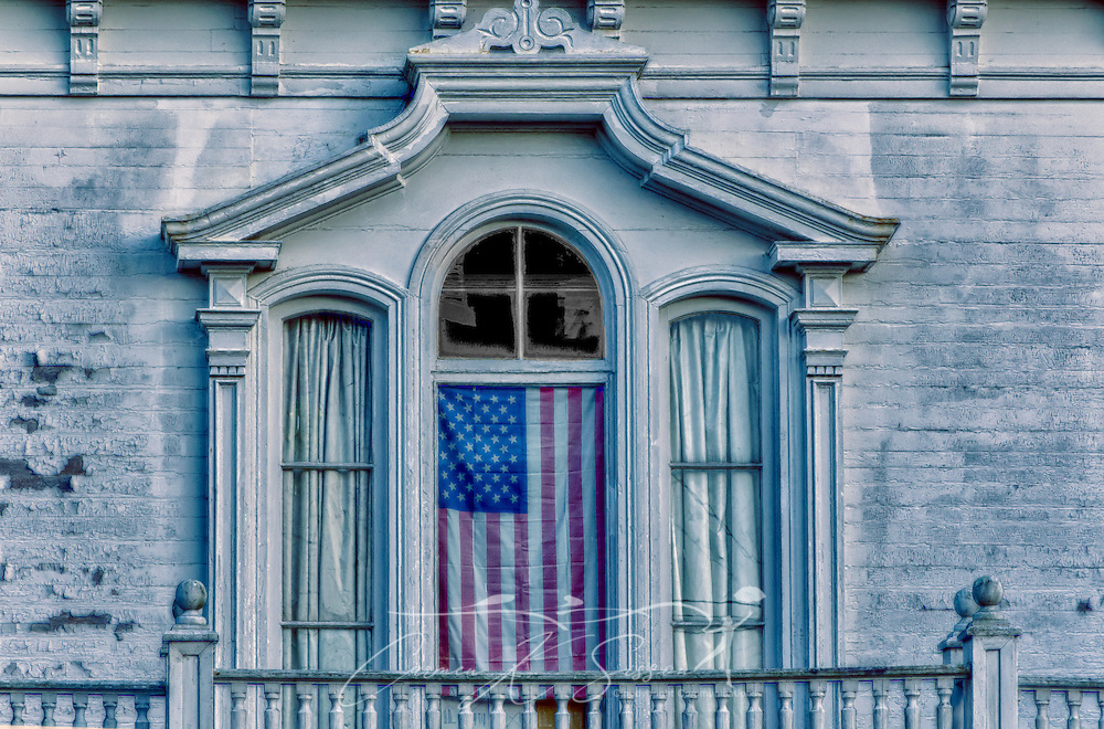 An American flag hangs in the window of a historic Southern antebellum home on Seventh Street North in downtown Columbus, Mississippi. (Photo by Carmen K. Sisson/Cloudybright)