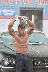 shirtless auto mechanic in the rain wringing out a shirt over his head