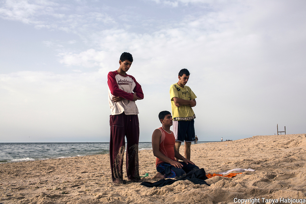 Three members of the Gaza Parkour team pray on the beach near their Khan Younis Refugee camp home. The beach is a favorite spot to practice more dangerous moves as the sand protects them.