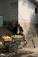 A peach seller counting his day take in the hutong behind the Bell tower. Beijing. China. October 2006