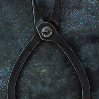 Vintage small pliers lying open on tarnished metal sheet