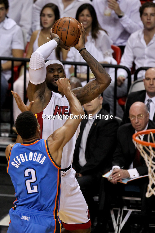 Jun 21, 2012; Miami, FL, USA; Miami Heat small forward LeBron James (6) shoots over Oklahoma City Thunder shooting guard Thabo Sefolosha (2) during the first quarter in game five in the 2012 NBA Finals at the American Airlines Arena. Mandatory Credit: Derick E. Hingle-US PRESSWIRE