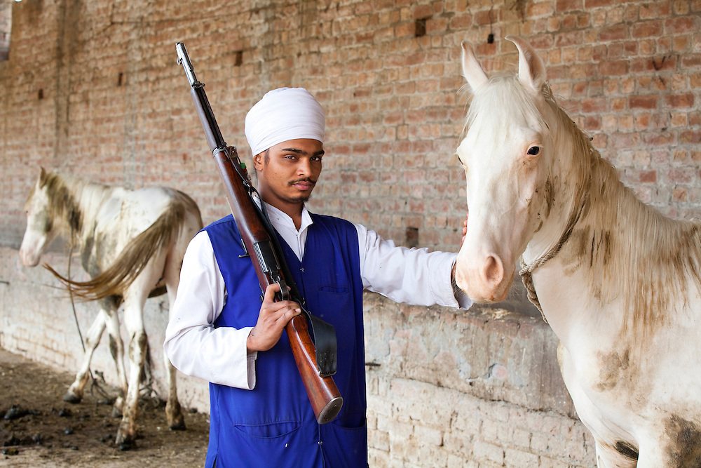 A young Niahng SIkh warrior standing next to his horse. The Nihangs are warrior sikhs and their attire consists of blue color. Many of the Nihangs own firearms.