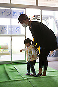A mother and her child at a warehouse that doubles up as an indoor playground for children and a food distribution centre for residents who fear eating the local produce and drinking the tap water. Minamisoma, Fuksushima Prefecture.