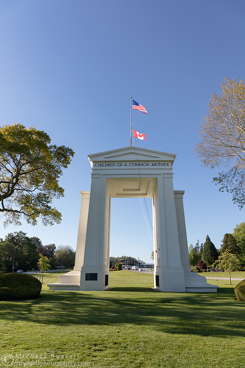 """The Peace Arch (1921) looking towards Canada.  Photographed from Peace Arch Historical State Park in in Blaine, Washington State, USA.  The Peace Arch was built in 1921 to commemorate the 100 year anniversary of treaties at the end of the War of 1812 between the USA and Great Britain. One side states """"Children Of A Common Motherr"""", the other """"Brethren Dwelling Together In Unity""""."""