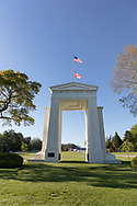 "The Peace Arch (1921) looking towards Canada.  Photographed from Peace Arch Historical State Park in in Blaine, Washington State, USA.  The Peace Arch was built in 1921 to commemorate the 100 year anniversary of treaties at the end of the War of 1812 between the USA and Great Britain. One side states ""Children Of A Common Motherr"", the other ""Brethren Dwelling Together In Unity""."