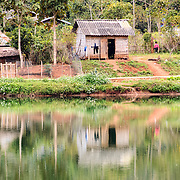 A woven bamboo house reflects on the still waters of a small lake in Vieng Xay in Houaphanh Province in northeastern Laos.