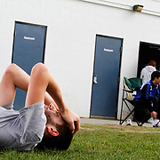 Hartford High School sophomore Mark Knapp, left, lay's on the ground after a 1600 meter run <br /> during track and field practice at Hartford High School on April 10, 2012.<br /> <br /> Valley News - Theophil Syslo