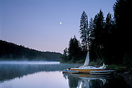 Moon at dawn over sailboat at Jenkinson Lake, Sly Park, El Dorado County, Sierra foothills, California