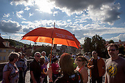 A travel guide with an umbrella and a group of tourist on Charles Bridge in Prague. The Charles Bridge (Czech: Karlův most) is a famous historic bridge that crosses the Vltava river in Prague, Czech Republic and is probably the Nr.1 tourists magnet in the city.