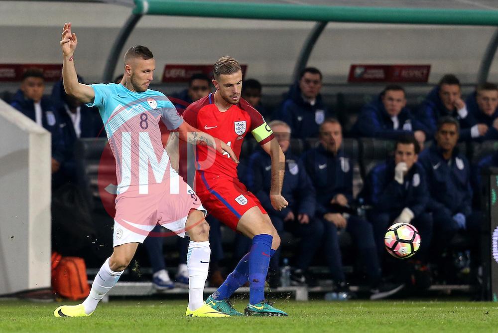 Jordan Henderson of England is tackled by Jasmin Kurtic of Slovenia - Mandatory by-line: Robbie Stephenson/JMP - 11/10/2016 - FOOTBALL - RSC Stozice - Ljubljana, England - Slovenia v England - World Cup European Qualifier