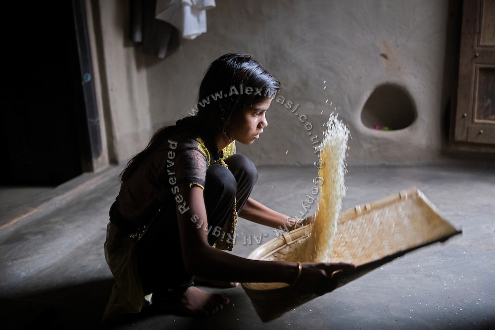 Tabasum Khatun, 14, is separating the wheat from the chaff, while preparing rice to be cooked for breakfast inside her home in Algunda village, pop. 1000, Giridih District, rural Jharkhand, India.