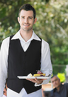 Waiter holding slice of pie at outdoor cafe