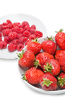Strawberries and raspberries over white background