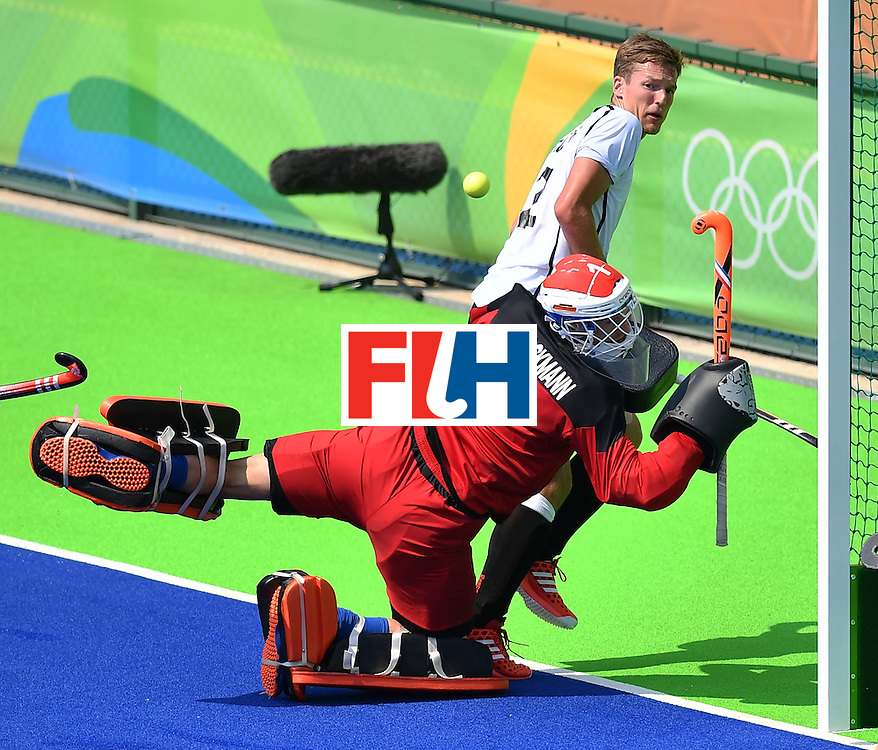 Germany's Mathias Muller (top) vies with Netherlands' goalkeeper Jaap Stockmann during the men's Bronze medal field hockey Netherlands vs Germany match of the Rio 2016 Olympics Games at the Olympic Hockey Centre in Rio de Janeiro on August 18, 2016. / AFP / MANAN VATSYAYANA        (Photo credit should read MANAN VATSYAYANA/AFP/Getty Images)