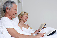 Middle-aged couple reading books in bed