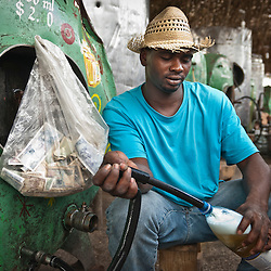 Man serving beer during a local party. Holguin, Cuba, Caribbean.