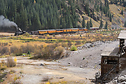 Durango & Silverton Narrow Gauge Railroad steam train passing an abandoned mine along the Animas River in Southwest Colorado.