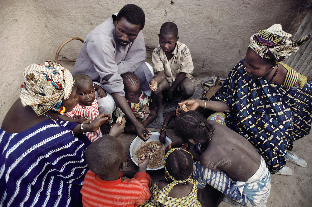 The children and adults in the two households of the Natomo family squat in the shady courtyard of the main house and share their communal dinner of fish and smoked rice.   Published in Material World, page 18-19. The Natomo family lives in two mud brick houses in the village of Kouakourou, Mali, on the banks of the Niger River. They are grain traders and own a mango orchard. According to tradition Soumana is allowed to take up to four wives; he has two. Wives Pama and Fatoumata are partners in the family and care for their many children together. Material World Project.