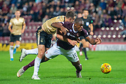 Andy Considine (#4) of Aberdeen FC drags Uche Ikpeazu (#19) of Heart of Midlothian FC to the ground on the edge of the box during the Betfred Scottish Football League Cup quarter final match between Heart of Midlothian FC and Aberdeen FC at Tynecastle Stadium, Edinburgh, Scotland on 25 September 2019.