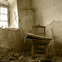 An abandoned home in Andalucia, Spain. The walls are crumbling from age and neglect. A suitcase and shoes were left behind.