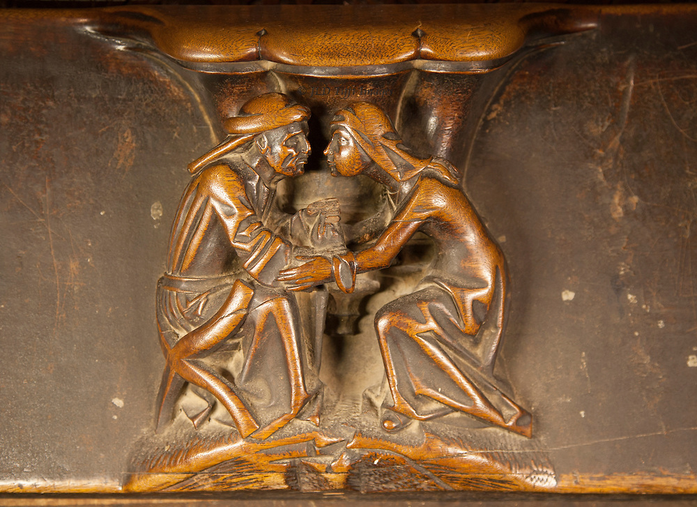 Toledo misericord: man and woman, heads close together in profile, in earnest conversation.  Their arms are joined in apparently affectionate contact.