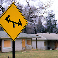 A playground sign stands in front of abandoned housign awaiting demolition.