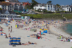 © London News Pictures. 06/07/2013 . Cornwall, UK.  Brits enjoy the warm weather on Gyllyngvase beach in Cornwall. 6th July 2013. Photo credit : LNP