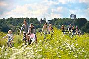 Nederland, Nijmegen, 5-8-2016 Mensen, een jong gezin, maken een fietstochtje over de dijk langs de Waal, Rijn in de Ooijpolder . Het is een mooie dag met zon en een blauwe lucht met wolken. Volgende week start weer een fietsvierdaagse . FOTO: FLIP FRANSSEN