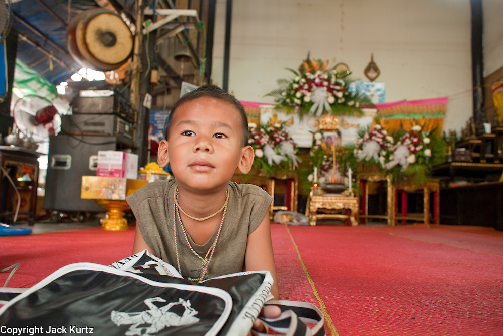 """Mar. 21, 2009 -- BANGKOK, THAILAND: A boy waits for a funeral to start in his home in the Monk's Bowl Village. The Monk's Bowl Village on Soi Ban Baat in Bangkok is the only surviving one of what were originally three artisan's communities established by Thai King Rama I for the purpose of handcrafting """"baat"""" the ceremonial bowls used by monks as they collect their morning alms. Most monks now use cheaper factory made bowls and the old tradition is dying out. Only six or seven families on Soi Ban Baat still make the bowls by hand. Most of the bowls are now sold to tourists who find their way to hidden alleys in old Bangkok. The small family workshops are only a part of the """"Monk's Bowl Village."""" It is also a thriving residential community of narrow alleyways and sidewalks.     Photo by Jack Kurtz"""