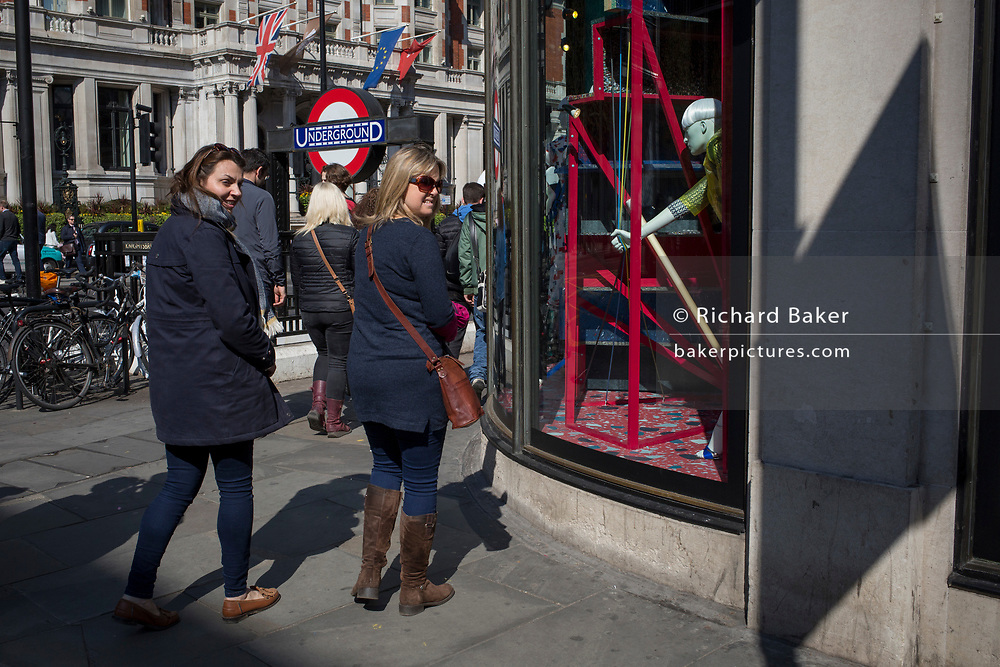 Passers-by walk outside the Harvey Nichols department store on the corner of Knightsbridge and Sloane Street, on 11th April 2019, in London, England.
