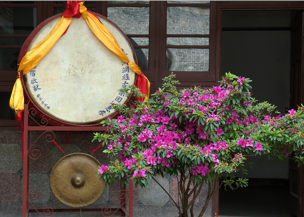 A traditional ceremonial drum stands alongside a brightly flowering bush inside the hotel courtyard. These courtyards are designed to allow for considerable privacy and quiet, a bit of a sanctuary from the bustle just outside the walls.