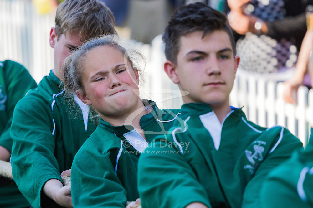 Westminster, London, June 6th 2016. A girls's face displays the competitiveness as teams from uk industry as well as the House of Commons and the House of Lords compete in the annual McMillan Cancer Charity tug o' war.