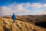 View over the Moffat Hills on a clear day, with a man in a blue jacket in the foreground, Annandale Way