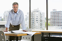 Business man leaning on desk in office