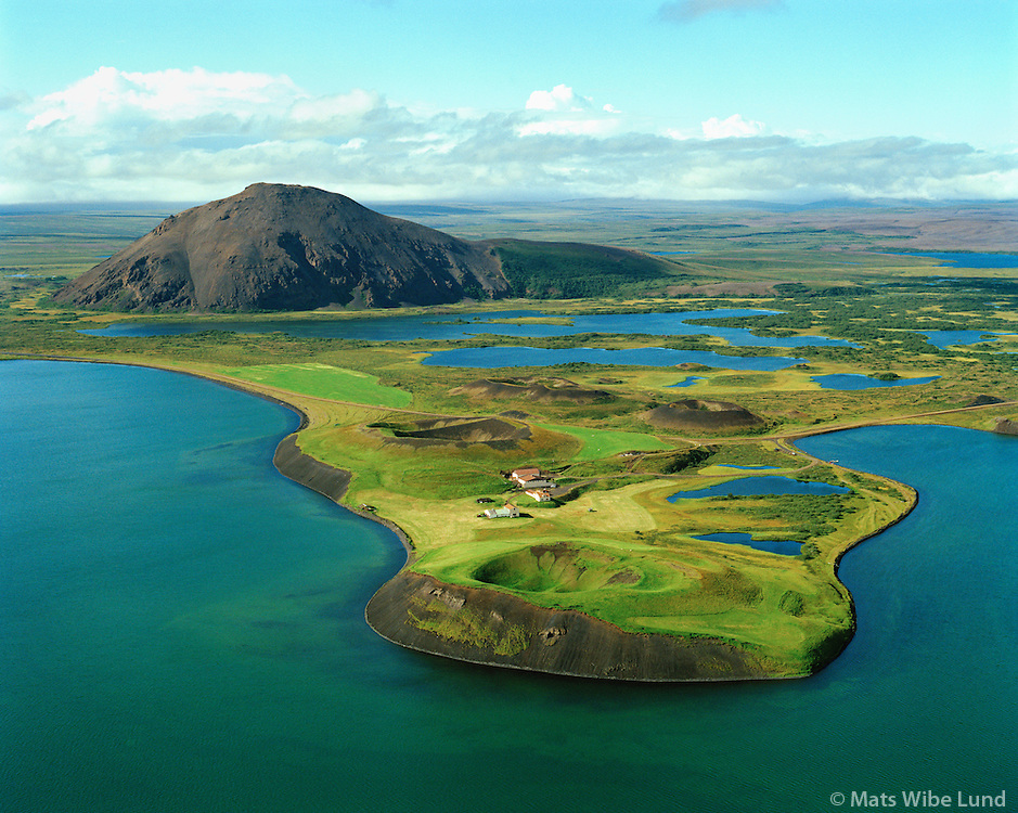 Vindbelgur sveitabýli og fjall með sama nafni. Séð til norðvesturs Mývátn, Skútustaðahreppur /  Vindbelgur farm and mountain with the same name. Vindbelgur -  .acutally means bellows (a pair of bellows). The craters in foreground are pseudocarters which came to beeing when the lavaflow poured into the lake Myvatn. Skutustadahreppur