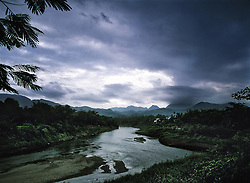 River flows through a mountainous landscape under a stormy sky, Luang Prabang Province, Laos, Southeast Asia