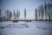 """A group of visitors beside the ruins of one of the crematoriums of Auschwitz II/Birkenau where lies a pond with 4 gravestones with the inscription in 4 different languages: """"To the memory of the men, women, and children who fell victim to the Nazi genocide. In this pond lie their ashes.  May their souls rest in peace.""""."""